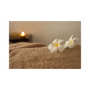photo of flowers on massage table with candle burning in background